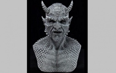 a terracotta grey bust of a scaly devil.